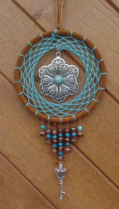 This is a hand made, hand woven, one of a kind, dreamcatcher. It is wrapped with red tan leather and woven with turquoise string. It is embellished with a large silver flower with intricate detail and a traditional turquoise center. It includes hand beading and a silver key hanging from the bottom. A new spin in traditional native art. Ideal for any room in the house and for anyone who enjoys native american goods. 5x5 center ring, 9 length.  NOTE TO INTERNATIONAL CUSTOMERS - If we are…