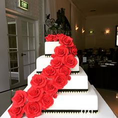 Handcrafted red sugar roses adorn this gorgeous four tier cake