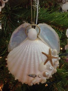 Our Artist Angels are all Unique and handmade here at Sea Things in Ventura CA. Each Angel has a Beautiful Scalloped Seashell skirt decorated with a pattern of