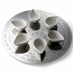 This #Seder collection from Laura Cowan is called The Ripple Effect: not only does the mirror-polished stainless steel and porcelain cups look like delicate petals on the surface of a pond, the words to Ma Nishtana, inscribed in #Hebrew, spiral into the center of the platter. The dishes are magnetized to be arranged however you want.
