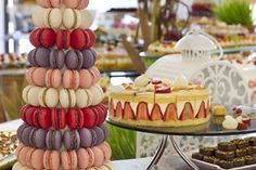 Macarons in pink, white, violet and magenta spiral upward in a tower formation next to a platter of strawberry cake