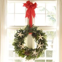 From Land to Sea: Blend accessories from your yard, such as pinecones, into a wreath with sea stars. Christmas wreaths provide a unique way to display your shell or sea-star collection. The punch of red in the wreath's ribbon unites with the room's red accents found in various patterns and throws. Wreath available at home supply stores. Ribbon available at craft supply stores.