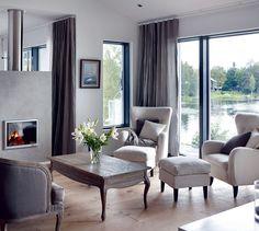 Olohuoneen takkanurkkauksessa huonekalut ovat muotokieleltään koristeellisempia. Puureunainen sohva sekä sohvapöytä ovat Pentikistä. Nojatuolit raheineen ovat Bloomerista. Novafloorin tammilankkulattia sävytettiin Osmo Colorin öljyvahoilla harmahtavaan taittuvaksi, jotta tammen keltaisuutta saataisiin häivytettyä.