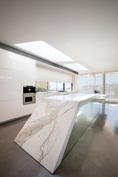 """""""The most impressive element of the interior is made of natural stone kitchen counter top, which cuts into the floor at an angle."""""""
