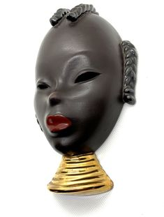 mask / wall mask of an Oriental Black Beauty by GOLDSCHEIDER which shows the beautiful face of a young Beauty with beautiful red lips and a fine gilded neck; the mask is marked on the backside GOLDSCHEIDER, made in Germany and numbered 701  #goldscheider #wallmask #orientalbeauty #goldscheidervienna #artpottery #artceramic #wandmaske #vintageshop_vienna #kunst19bybg