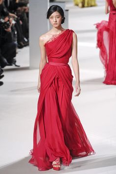 Elie Saab red. almost modest- i love one shoulder. it could look the same with a nude color cap sleeve on the other shoulder and draping a little furthur down the shoulder that already has a sleeve.