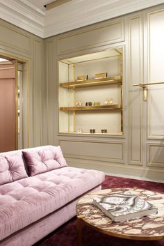 Power pink tufted velvet couch, seriously gorgeous marble coffee table, gold built in bookcase with matching gold trimmed moudlings!