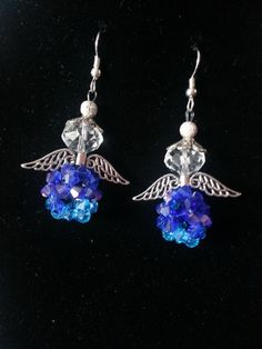 Hand made Angel ear rings . The bead ball is made of 4mm Blue and Light blue bicone swarovski glass beads. The angle wears a Tibetan Flower Top and the wings are Tibetan Sliver Wing Hollow spacers charms. All makes up to a special Christmas gift