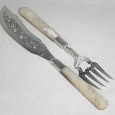 Antique Victorian sterling silver fish serving knife and fork set, having hand-carved mother-of-pearl handles, with hand-pierced and hand-engraved blade and tines with floral decoration. Made by Foxall & Co., of London in 1852. The dimensions of this fine hand-made silver fish serving set are length of knife 32 cms (12.5 inches), and length of fork 25.5 cms (10 inches).