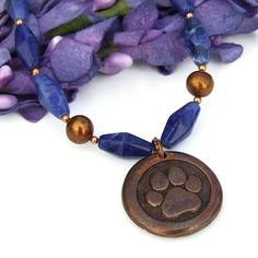 The beautifully meaningful two sided pendant featured in the DOG LOVE handmade necklace combines a dog paw print on one side and St. Francis on the other. To highlight the copper over pewter wax seal style rustic pendant, rich blue sodalite, lustrous freshwater pearls and glowing copper was used.