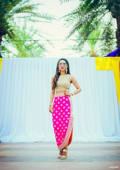 Mehendi Outfits - Harit & Eshanka | WedMeGood | Gold Blouse with Pink One Side Slit Skirt #wedmegood #indianbride via @topupyourtrip