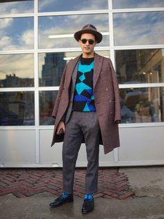 Un manteau et pantalon sobre jusqu'à ce qu'on arrive sur ce pull et ces chaussettes. La tenue reste maîtrisée car les couleurs turquoises sont bien calmées par d'autres moins criardes. Si vous débutez restez sur des chaussettes noires et commencez l'évolution par des chaussettes pourpres, facile à intégrer avec un costume bleu marine par exemple.