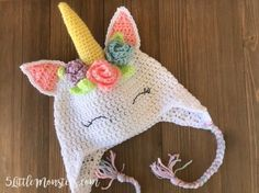 A free pattern for an adorable crocheted unicorn hat with flowers and leaves surrounding the horn.