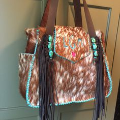 The Bonnie Bag, stitched in turquoise leather lace, with the owner's monogram on the flap and a pink suede heart underneath. Exterior side pockets and hand cut fringe complete this bag. From gowestdesigns.us