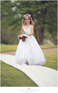 Adorable flower girl in a white dress with an aqua blue sash. Chelsea + Daniel's wedding at Lenora's Legacy. Image credit: Michelle Brooks Photography.