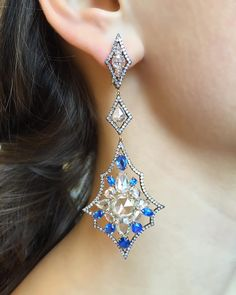 """Four layered snowflake inspired earrings featuring blue spinels and rose cut…"