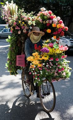 Amazing how this person is able to balance the vast array of flowers... bet you this is a very smelly bike.