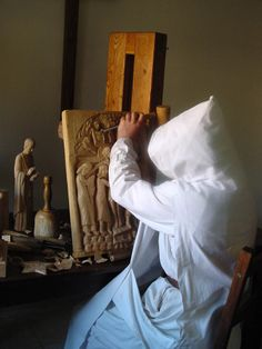 Monk creating a sculptural wood carving