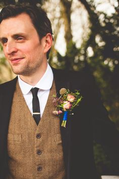 A groom with a tweedy vest and a hint of blue.