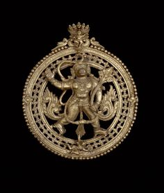 Circular plaque depicting a striding Hanuman, who is carrying in his left hand the magic plant - Sanjeevani which will cure Lakshmana (wounded on the field of battle). The flaming wheel and conch-shell seen at the edges of the circular surround, and the dancing figures at the top (either Krishna or Balarama), reinforce the Vaishnava context of the scene depicted. These were worn around the neck by itinerant mendicants or pilgrims. Made of bronze. Height: 21 centimetres Width: 17.5…