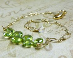 Bright green natural peridot gemstones are expertly wire wrapped with 14k gold filled wire and accented with lime green peridot stones and champagne Swarovski crystals. Peridot gemstones are finely faceted, eye clear quality and in a perfectly round shape.  What a lovely gift for a woman who loves lime green hues and real gemstones. Elegant and feminine, this bracelet will dress up any outfit from work to play! A thoughtful present for a woman born in August since peridot is her birthstone…