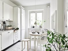 White kitchen in a cosy Swedish home in neutrals55Kvadrat / Anders Bergstedt / Emma Fischer.