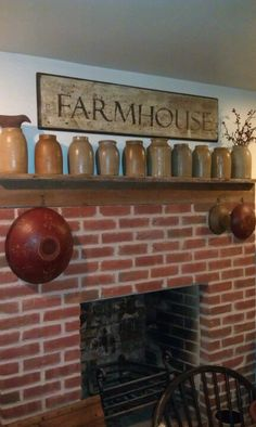Fireplace in the kitchen with antique canning crocks on the mantle  LORI TRIPLETT