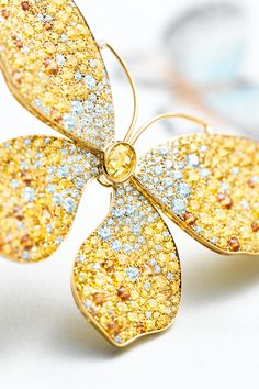 Butterfly ring in platinum and 18k gold with round brilliant yellow and white diamonds and spessartites. By Tiffany