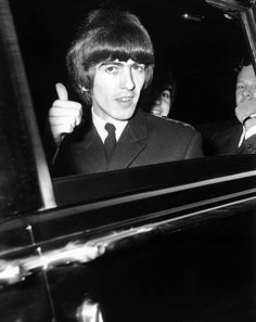 George Harrison of the Beatles gives a 'thumbs up' sign from his car window whilst on his way to Buckingham Palace to collect an MBE 26th October...