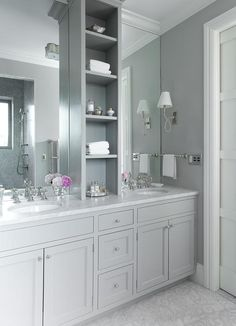 Grey master bathroom features gray shaker washstands topped with white marble fitted with his and her sinks under full height frameless mirrors flanking a grey shelving unit alongside a mosaic marble floor.