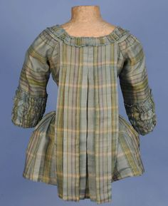 PLAID SILK PET-EN-LAIR JACKET, 18th C. Pale blue, green, cream and purple plaid having rounded front neckline squared in the back above Watteau pleats, short sleeve with bands of self ruching, neck and front trimmed with furbelows, inverted side pleats and linen lining.