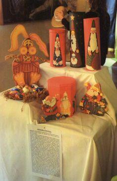 Latas con figuras de Papá Noel. Papá Noeles de madera y conejo de Pascua con huevos de yeso, todo pintado con acrílico con motivos del fok americano.
