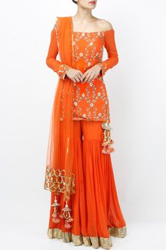 Featuring an orange off shoulder full sleeved kurta based in georgette with zardosi work and sequin embellished sleeve cuff. It comes with a pair of solid sharara with gold border. It is paired with a matching dupatta in net with sequin work and tassels. Fabric: Georgette, Net Care Instructions: Dryclean only.