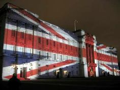 Buckingham Palace with the Union Jack projected onto it for Christmas Eve
