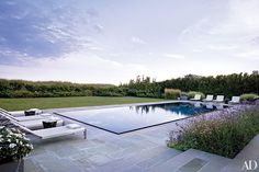 A bluestone terrace surrounds the pool at an idyllic Long Island, New York, beach house designed by architect Thomas Kligerman and decorator Elissa Cullman.  Pin it.