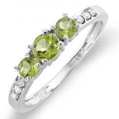 Celebrate your past, present and future together with this classic green peridot engagement ring. Glimmering with a trio of brilliant round diamonds and delicate diamonds along the polished 10 karat white gold band, this beautiful ring comes to a total carat weight of 0.50 carat. Chic and elegant, this will make an engagement ring that will never go out of style.