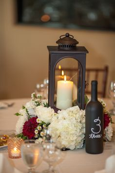 Paint wine bottle with chalk paint and write table number. Cute and inexpensive. With pink flowers instead of the red ones