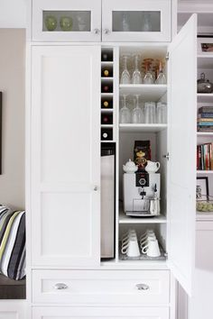 A coffee and wine bar is tucked into one of the pantry units; small glass-panel doors up top help lighten the look of tall cabinetry. | Photo: Stacey Brandford | http://thisoldhouse.com