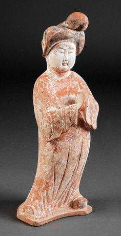 A Chinese Painted Pottery Figure of a Court Lady (height 22 in), Tang Dynasty (618-906), standing corpulent beauty modeled wearing loose voluminous robes and upswept thick coffure.