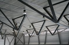 Splitting these trusses into V shapes reduced the span of the floor slab, and burying the top chord in the concrete floor compositely made a 30% saving in steel and reduced the quantity of suspended concrete in the building by 50%.