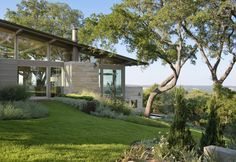 """Situated on a steep hill with stunning views of downtown Austin, Hillside House reflects the owner's desire to have a """"right sized"""" sustainable home that embraces outdoor living. All areas of the house were designed to flow directly into the landscape, with ample porches, gardens and outdoor living spaces. Terraced directly into the hill, the upper level includes the master bedroom and main living areas. A green roofon the lower children's wing created a generous main-level…"""