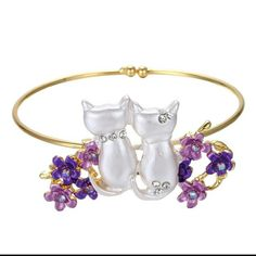 COMING SOON! CATS IN PURPLE FLOWERS BRACELET Gold bracelet with 2 white cats surrounded by purple flowers. Crystals sprinkled throughout design. Material is zinc alloy. Diameter is a little over 2 inches Jewelry Bracelets