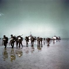 These Canadian soldiers unload on the beaches of the sector of Juno Beach, June 6, 1944, with their equipment. In background, two LST discha...