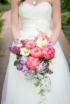 A colorful wedding bouquet with coral peonies, yellow tulips, and fresh lilac.