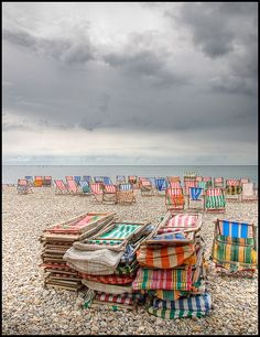 Deck chairs and storm clouds. Remember covering our belonging with plastic macs and deckchairs and heading for the water when it rain.