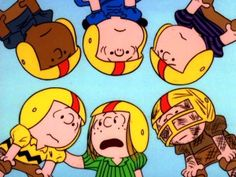 In a team huddle, player-coach Peppermint Patty tells placekicker Chuck the plan, while teammates Franklin, Lucy, Shermy, and Pig Pen listen in.