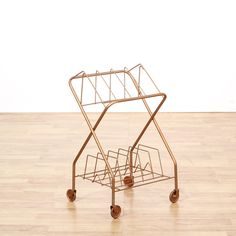 This mid century modern magazine rack is featured in a durable metal with a shiny copper painted finish. This record rack has x-shaped side legs, rolling wheel feet and bent slot storage. Unique cart great for storing books and records! #americantraditional #storage #magazinerack #sandiegovintage #vintagefurniture