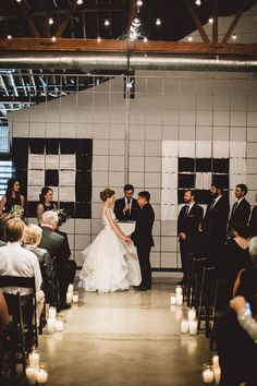 Industrial wedding ceremony with candle-lined aisle | Image by Kym Ventola Photography