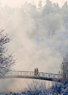 People walk on a bridge across the Bolshaya Almatinka river in Almaty, Kazakhstan