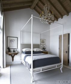 A chandelier by Maison Jansen, found in Argentina, hangs above a bed by Oly Studio in the master bedroom; the painting is by Andrew Bucci.